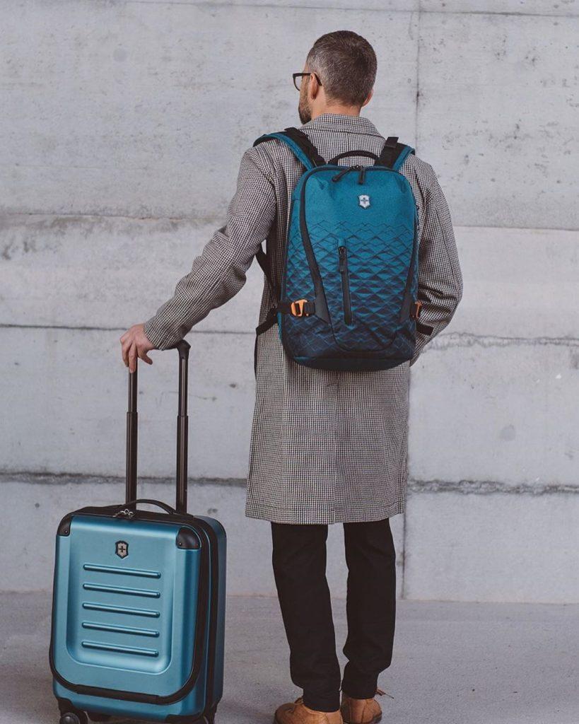 Синий рюкзак Victorinox с серым пальто